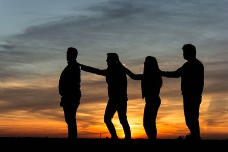 zest for life: People silhouette family standing together in the sunset Stock Photo