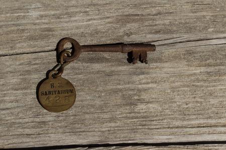 sanitarium: Old rusty skeleton key to a sanitarium  mental hospital on a wood bench