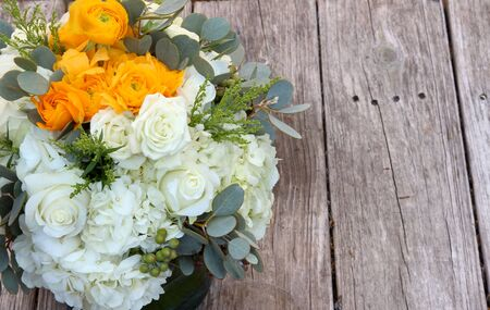 french countryside: Wedding bouquet of white and orange flowers on a rustic table in the French countryside on Valentines Day