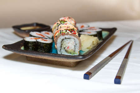 chop sticks: Sushi rolls, chop sticks, wasabi and ginger on a plate on white background Stock Photo