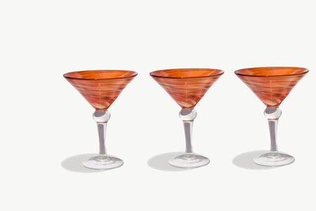 martini shaker: Three orange martini cocktail blown glasses and a shaker on a white background