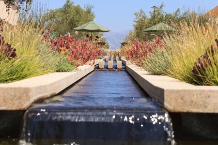 water garden: Trench style water fountain with a small waterfall and pond in a garden. Stock Photo