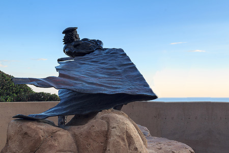 heaving: September 9, 2015. Dana Point, California: Life-size bronze of a hide Drogher, Richard Henry Dana, heaving cowhides off the cliffs to ships in Dana Point harbor, summer sunset. Editorial use only.