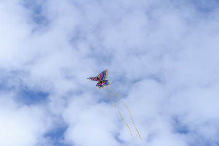 bloating: A rainbow colored butterfly kite flies across a blue sky in summer