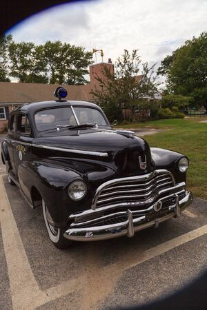 deluxe: Orleans, Massachusetts, Cape Cod  - September 22, 2015: Black classic Chevrolet Special Deluxe police car parked in front of the Orleans police department. Editorial use only.
