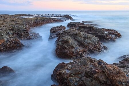 rocks water: Sunset over the rocks at Shaws Cove in Laguna Beach as water flows over the stone Stock Photo