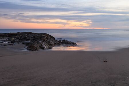 Sunset over the rocks at Shaws Cove in Laguna Beach as water flows over the stone Archivio Fotografico
