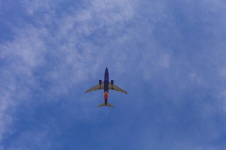 editorial: Newport Beach, California October 19, 2015: Airplane takes off into the blue sky on a fall morning. Editorial use only. Stock Photo