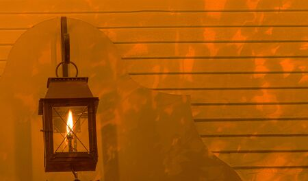 hearth and home: Lamp glows on the background of a house at night