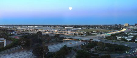 Irvine, California, February 26, 2016: Aerial view of John Wayne Airport in Orange County, California, at sunrise with a full moon and light trails across the 405 highway in front.