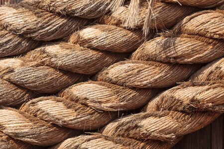 coiled rope: Golden burlap rope background coiled around a post on a boat dock in sunlight.