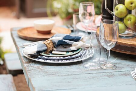 napkin ring: Rustic farm place setting with white and blue plates, napkins and clear wine glasses on a distressed country table on a patio in summer.