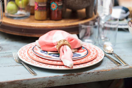 Rustic farm place setting with white and red plates, napkins and clear wine glasses on a distressed country table on a patio in summer.
