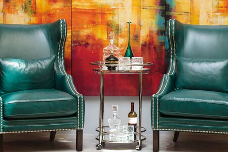 swanky: Orange, CA, USA — April 29, 2016: Alcohol decanter, bottle of Chambord liqueur, red wine and glasses on a glass serving table between two chic blue green leather chairs in front of a red, orange and yellow abstract painting.