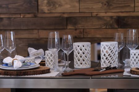 candleholders: Rustic place setting with white candleholders and wine glasses on a country patio in summer.