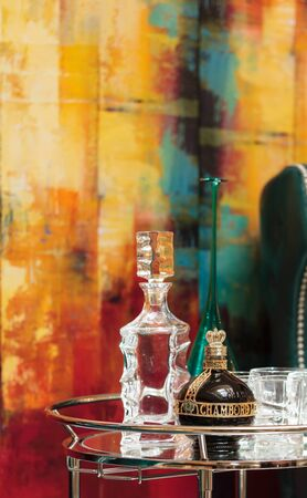 orange chairs: Orange, CA, USA — April 29, 2016: Alcohol decanter, bottle of Chambord liqueur, red wine and glasses on a glass serving table between two chic blue green leather chairs in front of a red, orange and yellow abstract painting.
