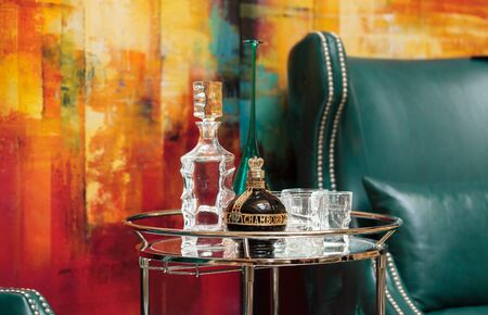 swanky: Orange, CA, USA — April 29, 2016: Alcohol decanter, bottle of Chambord liqueur, red wine and glasses on a glass serving table between two chic blue green leather chairs in front of a red, orange and yellow abstract painting. Editorial
