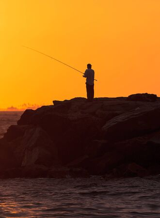 balboa: Silhouette of Man fishing on the pier off Balboa Island, Newport Beach at sunset in Southern California