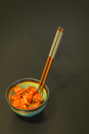 poke: Poke lunch bowl of spicy raw tuna sushi sashimi with chopsticks.