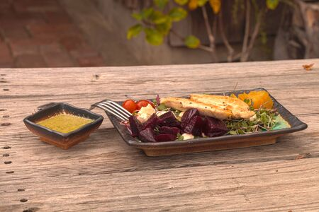 enzymes: Summer salad with micro greens, feta cheese, tomatoes, red and yellow beets, and chicken with a cilantro salad dressing on a rustic wood picnic table.