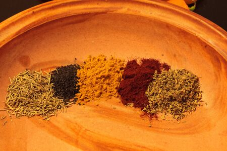 Mix of red cayenne pepper, yellow turmeric, green rosemary and oregano herbs with black sea salt on an earthy pottery plate.