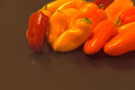 organic peppers: Red, yellow, orange colorful healthy organic peppers on a black background