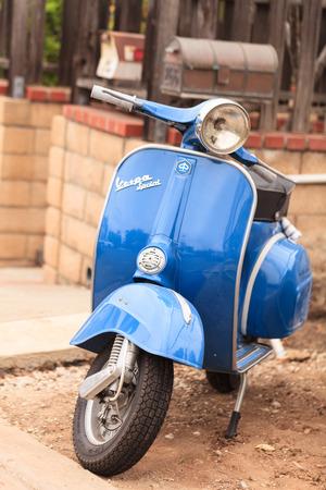 Laguna Beach, CA, EE.UU. - 23 de julio de 2016: Blue Vespa retro ciclomotor estacionado frente a una casa en Laguna Beach, California, Estados Unidos en verano. Solo para uso editorial.