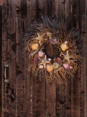 Seashell, starfish, heather and urchin wreath on a rustic wooden door background