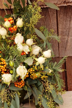 sprigs: Holiday flower bouquet inside a gourd vase with red berries, green leaves and sprigs, and white roses on a rustic wood farm house background. Stock Photo