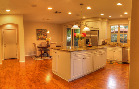 Irvine, CA, USA – August 19, 2016: Large kitchen with recessed lighting, wood floors, chrome stove, marble counter and feng shui decor. 스톡 콘텐츠
