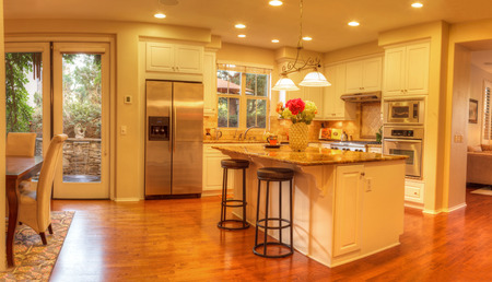 stovetop: Irvine, CA, USA � August 19, 2016: Large kitchen with recessed lighting, wood floors, chrome stove, marble counter and feng shui decor. Stock Photo