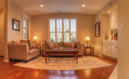 거실 소파, 커피 테이블, 램프, recessed 조명, 나무 바닥과 풍수 장식. 단순한 예술 작품은 소파 위에 매달려 있으며, 창문은 다른 소파 위에 있고 선반과