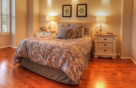 Irvine, CA, USA – August 19, 2016: Large master bedroom with recessed lighting, wood floors and feng shui decor. The bed has a tan pattern duvet comforter with fluffy pillows and simple art work above.