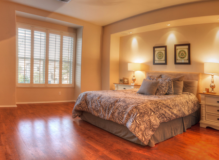 Irvine, CA, USA � August 19, 2016: Large master bedroom with recessed lighting, wood floors and feng shui decor. The bed has a tan pattern duvet comforter with fluffy pillows and simple art work above. Stock Photo