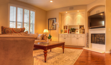 Irvine, CA, USA – August 19, 2016: Living room with a sofa, coffee table, lamp, recessed lighting, wood floors and feng shui decor. Simple art work hangs above the couch, a bay window is over another sofa and built in shelves and a fireplace are on the ot