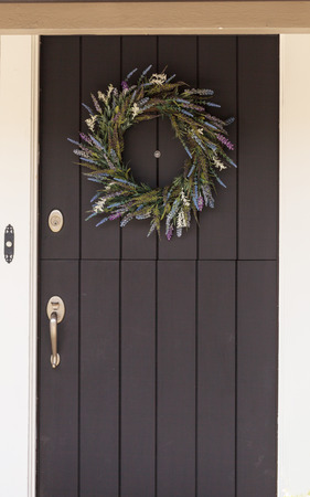 white trim: Black door with white trim and a purple, blue and green heather wreath hanging in the center