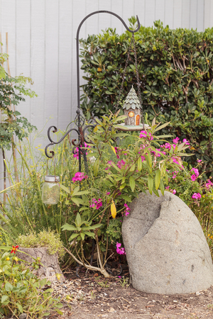 hook like: Birdhouse hangs from a garden hook stand over a boulder among flowers like geraniums and shrubs.