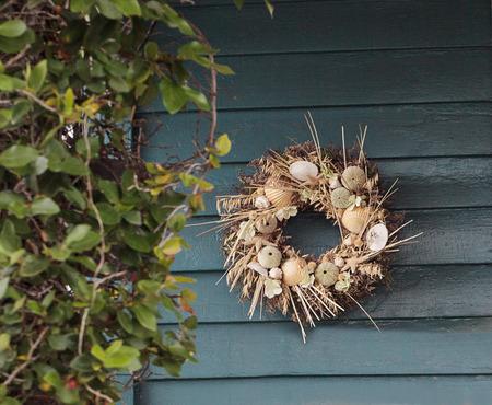 Seashell, starfish, heather and urchin wreath on a blue wooden door background Фото со стока