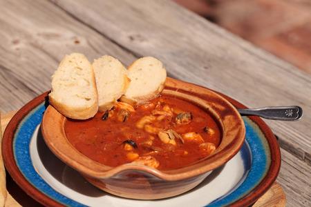 フランスパン、エビや魚、貝、ロブスター、カニ、皿やまな板の上に陶器ボウルのトマトソースでホタテとシーフード チョッピーノ。
