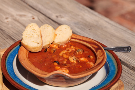 Seafood cioppino with French bread and shrimp, fish, clams, lobster, crab and scallops in tomato sauce in a pottery bowl on a dish and a cutting board. Stock Photo