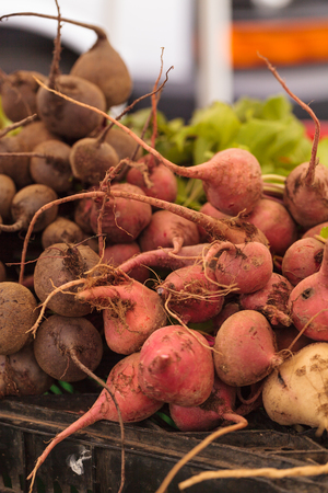 Organic red beets in a bushel of vegetables at a farmers market