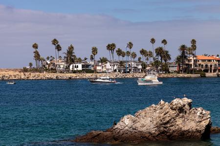 Boat leaving the harbor in Corona del Mar, California in summer