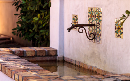 Classic rustic Italian fountain with a spout and pool of water below Banco de Imagens