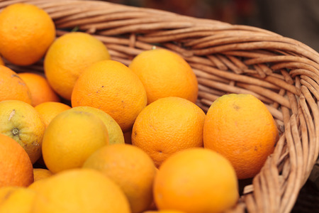 Fresh oranges in a fruit basket at a farmers market
