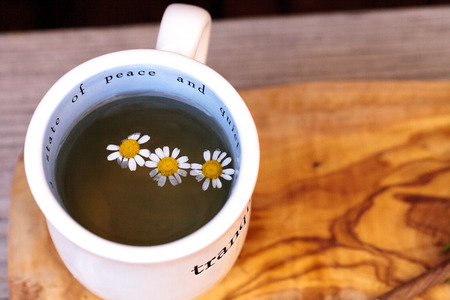 chamomile flower: Chamomile tea with chamomile daisy flowers in a hot white cup on a wooden rustic cutting board and a spoon. This home remedy is known to help sleep and aid a sore throat Stock Photo