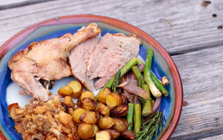 Rosemary roasted duck stuffed with bread stuffing and ringed with asparagus in a pottery dish during the holiday season. Stock Photo