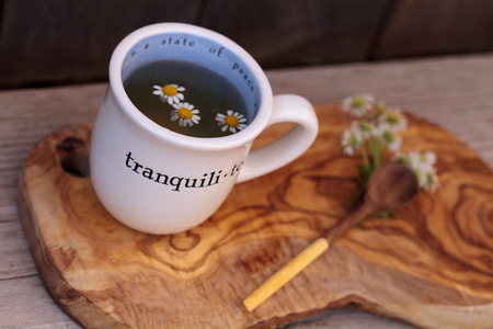 sore throat: Chamomile tea with chamomile daisy flowers in a hot white cup on a wooden rustic cutting board and a spoon. This home remedy is known to help sleep and aid a sore throat Stock Photo
