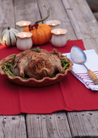 Rosemary roasted duck stuffed with bread stuffing and ringed with asparagus in a pottery dish during the holiday season Stock Photo