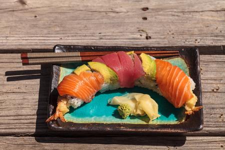 Dragon roll sushi with salmon, tuna, avocado, shrimp tempura and rice on a plate with chopsticks Stock Photo - 63998465