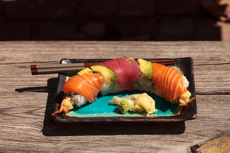 Dragon roll sushi with salmon, tuna, avocado, shrimp tempura and rice on a plate with chopsticks Stock Photo - 63998683